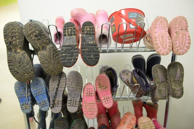 Foto: Schuhe und Stiefel der KiTa-Kinder und -beschäftigten hängen in Reihen auf einem Schuhständer.
