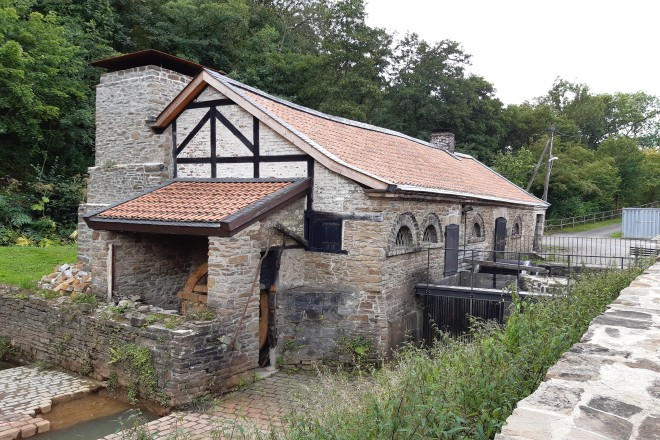 Foto:Ansicht des Eisenhammergebäudes. Das Gebäude hat eine Natursteinfassade und ein rot gedecktes Dach. Die Giebelwand besteht zum Teil aus Fachwerk, im offenen Vorbau erkennt man Teile des neuen Wasserrades, daneben den großen gemauerten Kamin.