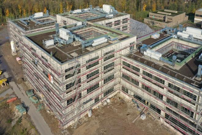 Foto: Das Foto aus der Vogelperspektive zeigt die fertiggestellten Dächer der vier Bauteile des Neubaus der Gesamtschule. Die Lüftungsgeräte sind auf den Dächern montiert und das Substrat der Dachbegrünung ist eingestreut.