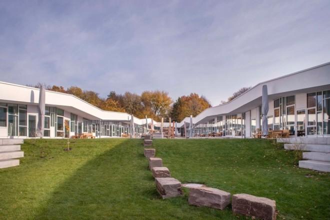 Foto: Außenansicht des Innenhofes der neuen Kindertagesstätte Lysegang von Westen. Das Bild zeigt einen durch die umgebenden Kita-Gebäude geschützten Innenhof mit verschiedenen Spielgeräten.