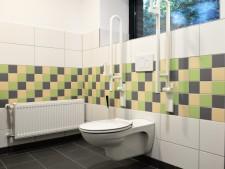 Foto einer barrierefreien Toilette im Toilettenneubau der Ludgerusschule. Der Raum wurde weiß gefließt, mit einem grün-, gelb- und graufarbigen Fliesenspiegel.