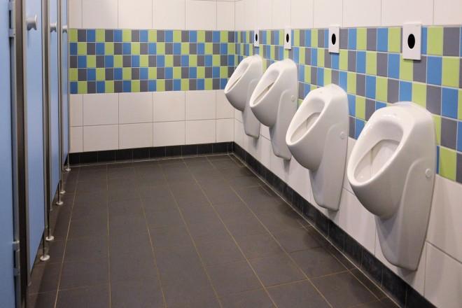 Foto Innenansicht der Jungentoiletten der Ludgerusschule in Essen-Werden nach Sanierung. Rechts im Bild vier Wandurinale, links WC-Eingangstüren.