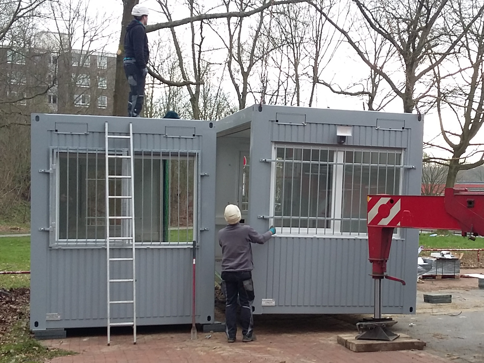 Foto: Es sind zwei Containerelemente zu sehen. Ein Elemtent wurde am Standort Bürgerhaus Oststadt bereits aufgestellt, ein zweites Element wird von einem Kran rechts daneben an den Aufstellort gehoben.