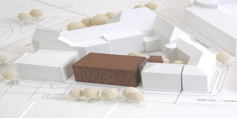 Foto: Wettbewerbsmodell Haus der Essener Geschichte. Inmitten weißer Gebäudemodelle sieht man das in brauner Farbe dargestellte Magazingebäude.