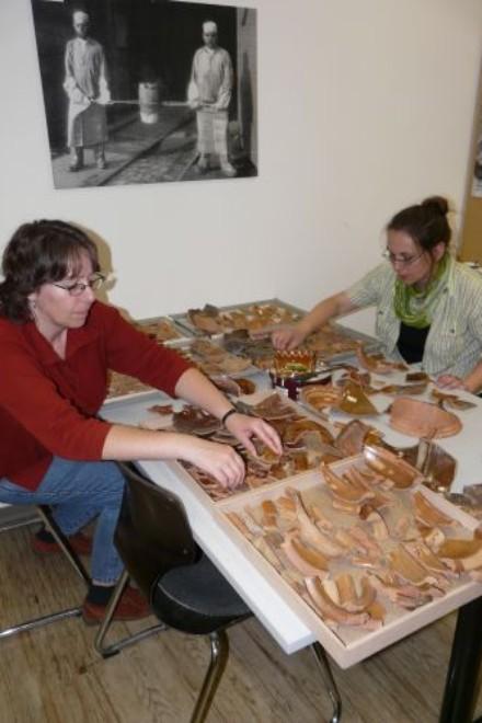Foto: Bianca Khil und Elke Schneider, M.A. beim Auslegen einiger Keramikfunde vom Gänsemarkt