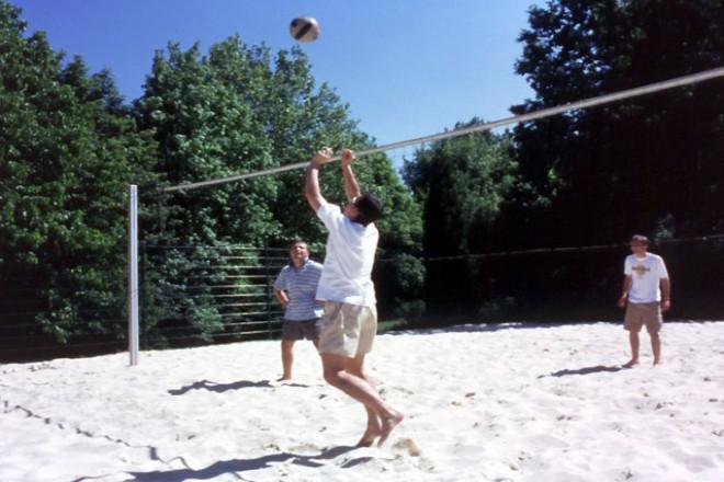 drei Personen spielen Beachvolleyball
