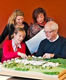 vier Personen begutachten ein Planungsmodell