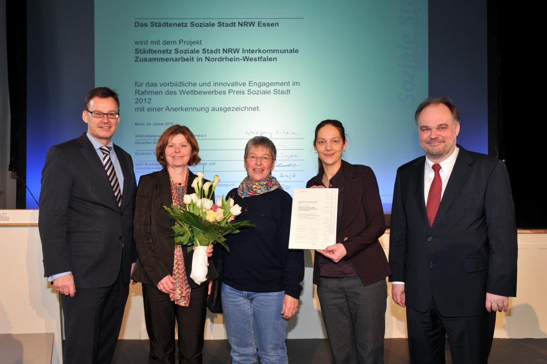 Foto: Zwei herren und dazwischen drei Damen mit Blumenstrauß und Urkunde vor einer Wandprojektion der Urkunde Preis Soziale Stadt 2012