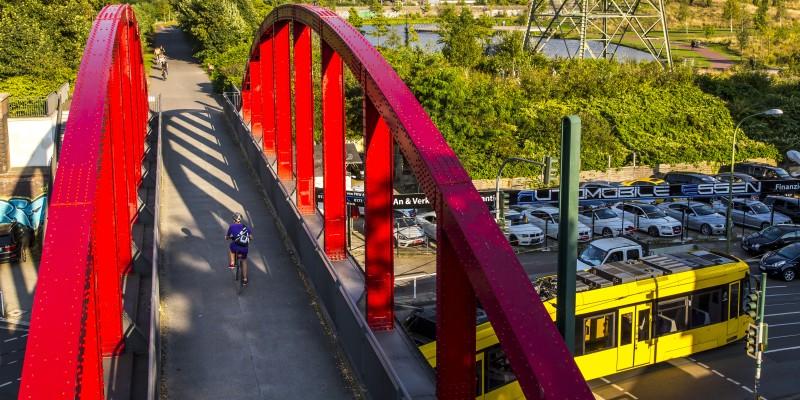 Fahrradfahrer fährt über Brücke, unter der eine Straßenbahn lang fährt