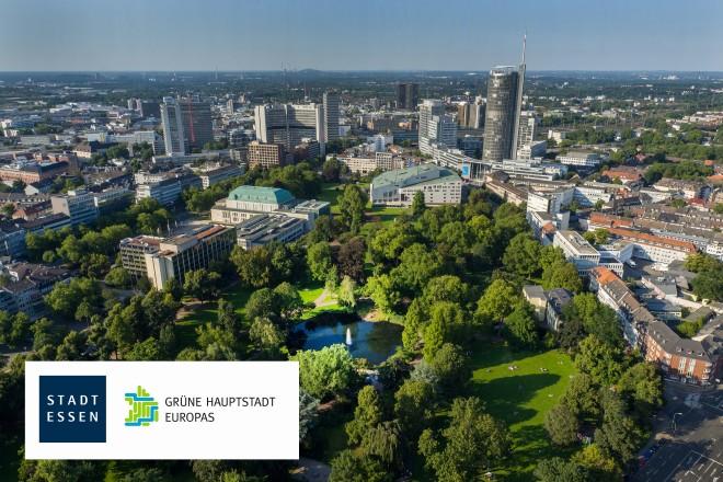 Fotomontage: Blick über den Stadtgarten mit Skyline im Hintergrund, davor graphischer Text 'Grüne Hauptstadt Europas'