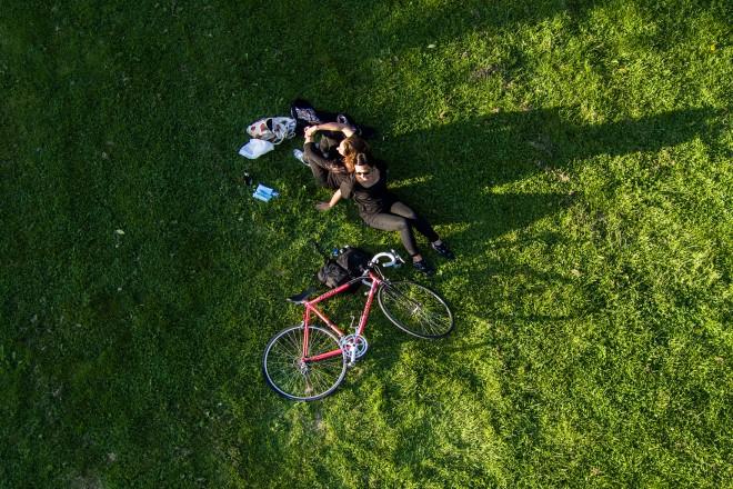 Luftbild: Zwei Menschen mit Fahrrad auf einer Grünfläche
