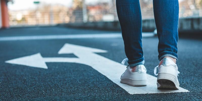 Foto: Eine Person, deren Füße nur zu sehen sind, geht auf einem Richtungspfeil, der in zwei verschiedene Richtungen zeigt.