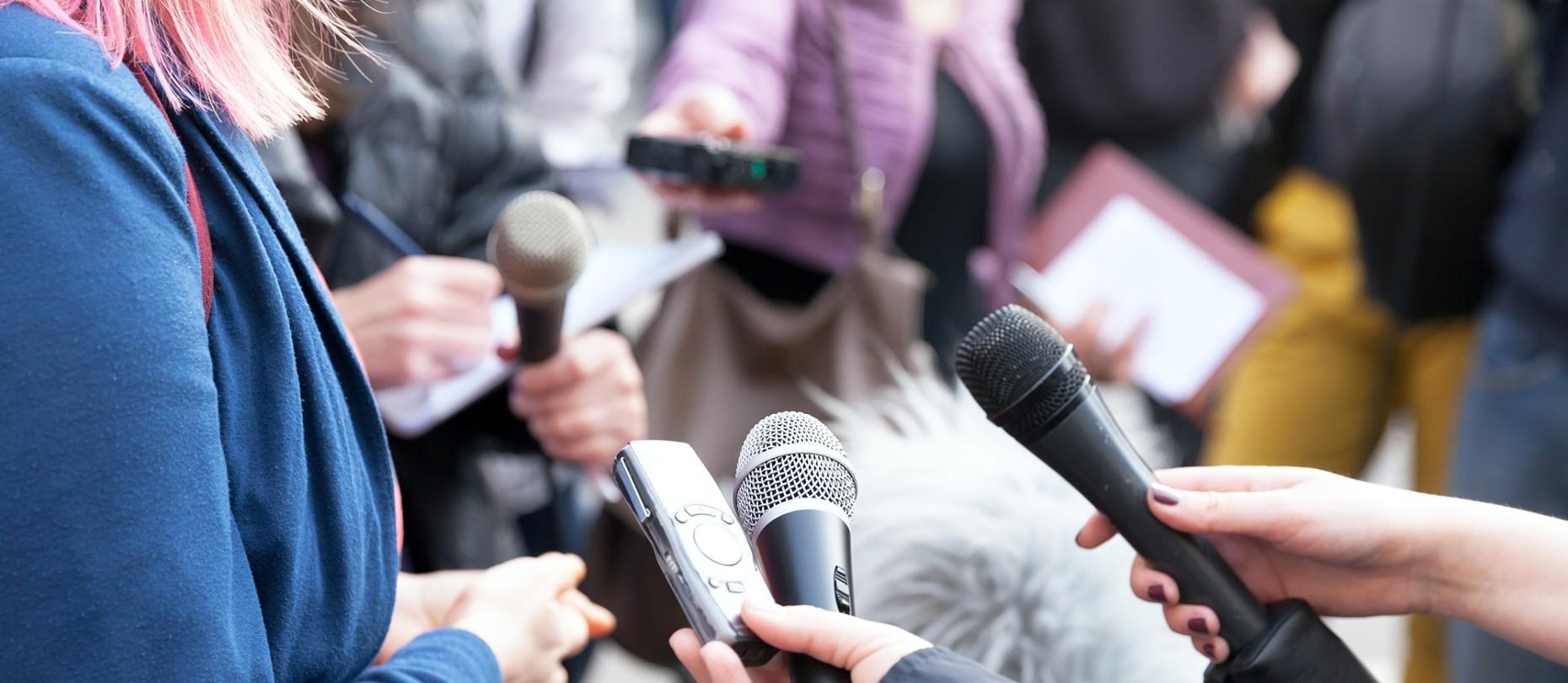 Foto: Mehrere Reporter halten einer weiblichen Person Mikrofone hin.