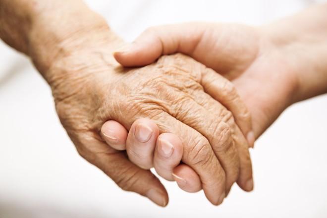 Foto: zwei haltende Hände, die Hand einer jüngeren Person und die einer älteren Person.