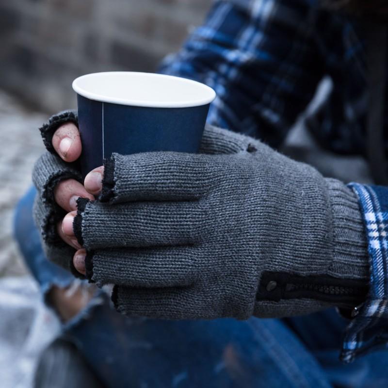 Foto: eine Person sitzt auf dem Boden und hält einen Kaffeebecher in beiden Händen.