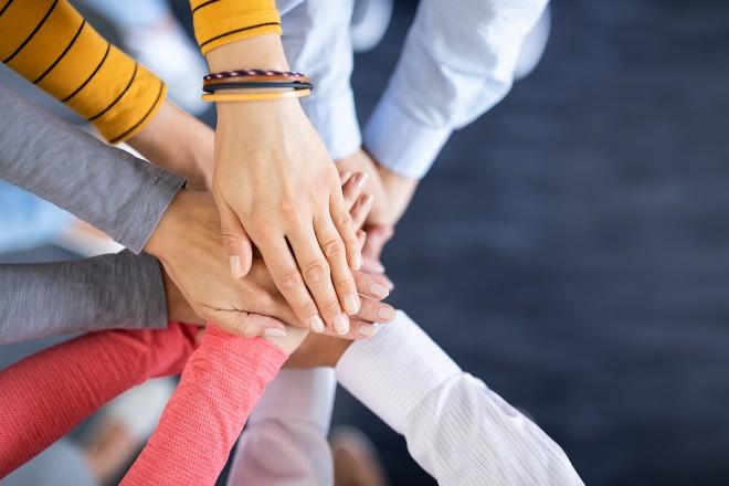 Foto: Verschiedene Personen eines Teams stapeln ihre Hände übereinander. Nur die Hände sind zu sehen.