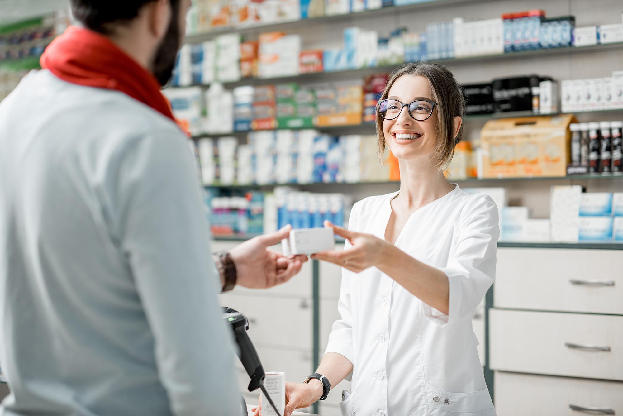 Foto: Eine junge Apothekerin reicht dem männlichen Kunden eine Medikamentenverpackung über den Tresen.
