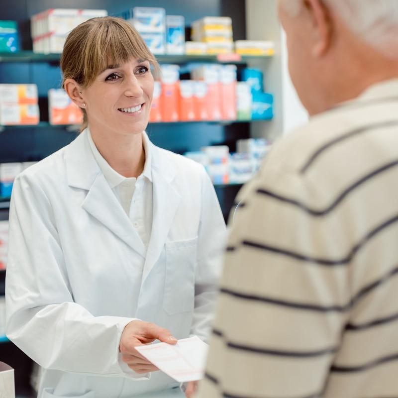 Eine Apothekerin nimmt ein Rezept von einem Kunden entgegen.