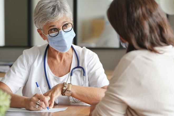 Foto: eine Ärztin mit Maske führt ein Beratungsgespräch mit einer Patientin