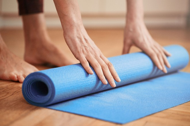 Foto: Eine Person rollt eine Yogamatte mit beiden Händen ein.