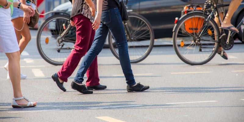 Foto: Eine Kreuzung an der Fußgänger und Fahrradfahrer die Straße überqueren.
