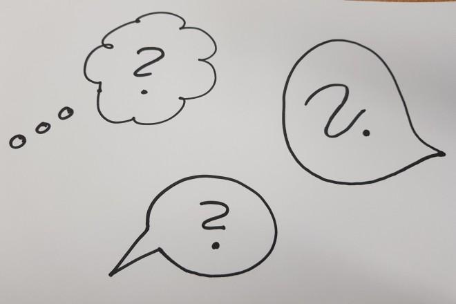 Foto eines weißen Blatt Papier mit aufgemalten Sprechblasen in denen Fragezeichen stehen