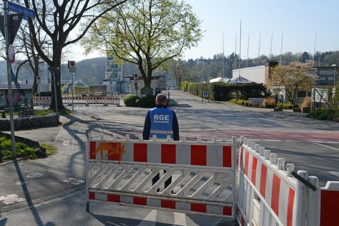 Foto: Ein Mitarbeiter der RGE Servicegesellschaft Essen mbH steht am abgesperrten Einmündungsbereich an der Freiherr-vom-Stein-Straße zum Parkplatz am Regattaturm.