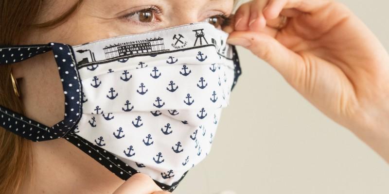 Foto: Anlegen eines Behelf-Mund-Nase-Schutzes