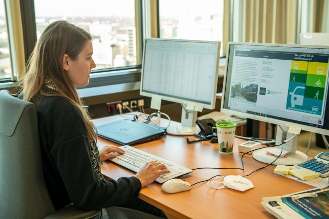 Foto: weibliche Person sitzt an einem Schreibtisch vor zwei Monitoren und hat die Seite des Bürgerforums unter essen.de geöffnet
