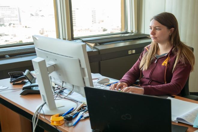 Foto: weibliche Person sitzt am Schreibtisch und schaut auf ihren Monitor