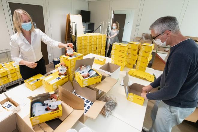 Foto: zwei Personen packen Päckchen für die Teilnehmenden des Bürgerforums