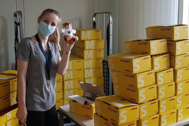 Foto: Mitarbeiterin der Stadt Essen winkt mit Stofftier, das den Bürgerpaketen beigelegt ist