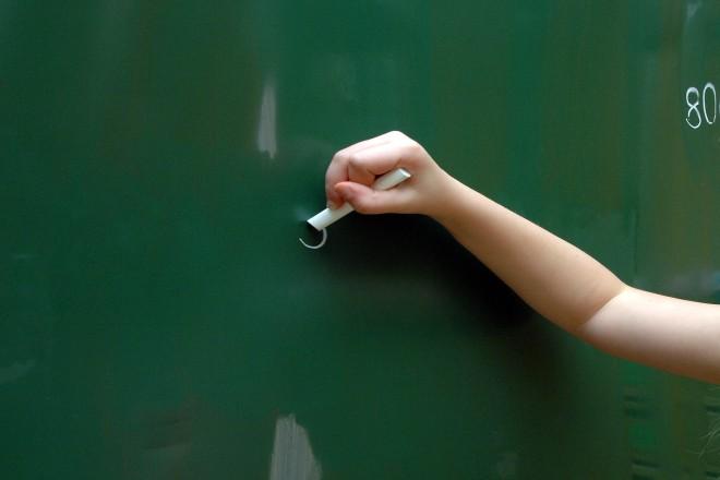Foto: Hand malt auf Tafel in einer Schule
