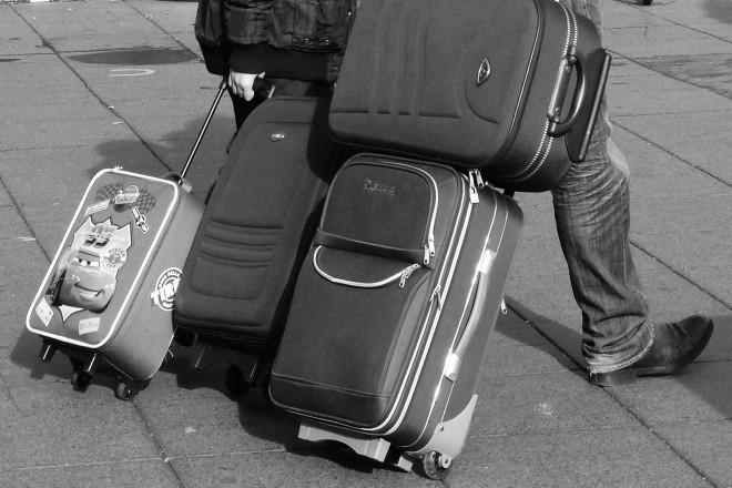 Foto: Zwei Menschen die vier Koffer hinter sich herziehen