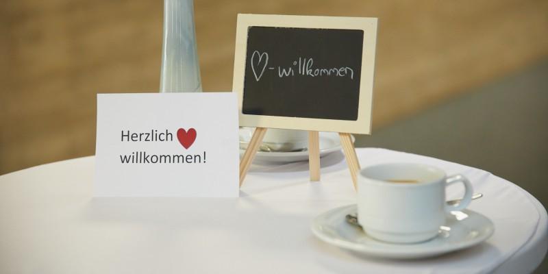 """Foto: auf einem Tisch stehen Kaffetassen, sowie eine Blumenvase und zwei Schilder mit den Worten """"Herzlichwillkommen!""""."""