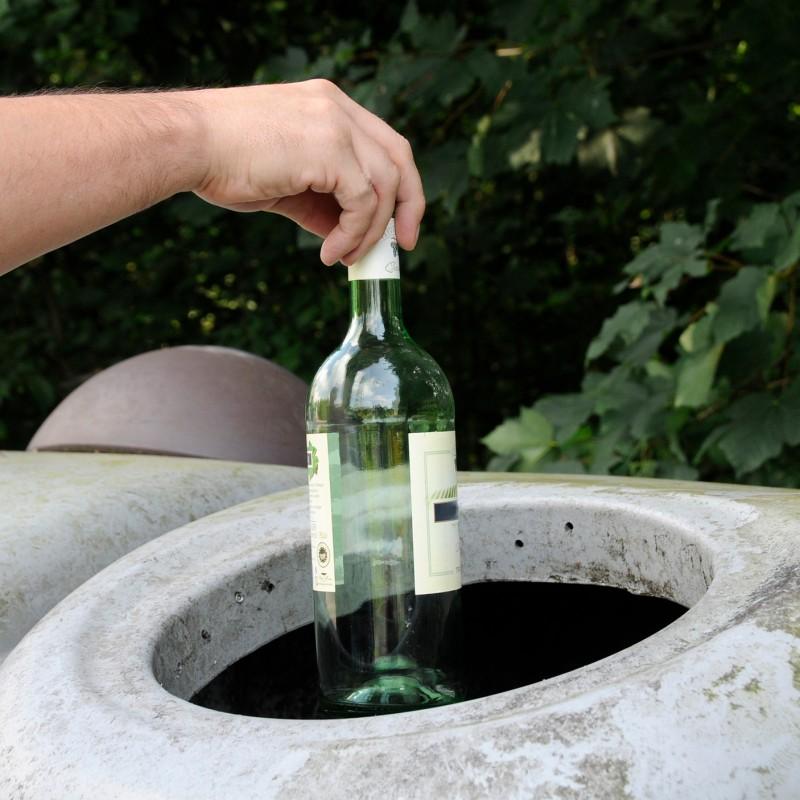 Foto: Flasche die in einen Glascontainer geworfen wird