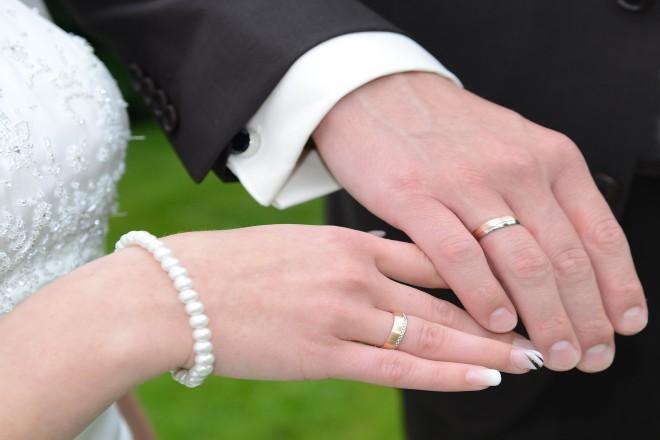Zwei Hände mit Ehering berühren sich.