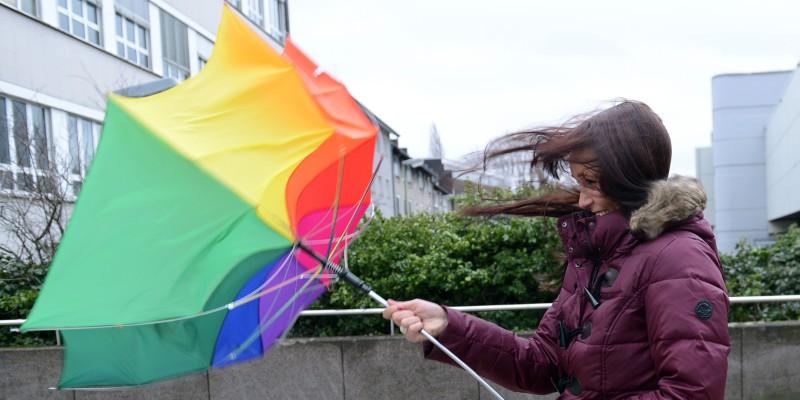 Foto: Person mit Regenschirm im Sturm