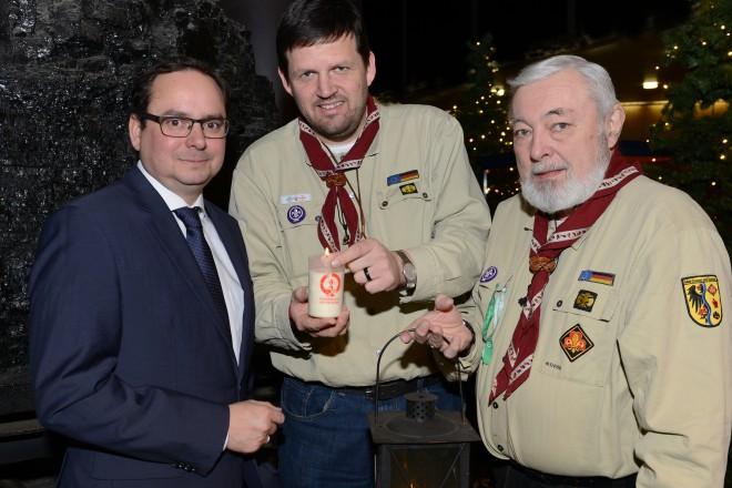 Matthias Feldmann ( Mitte ) und Reinhard Osterfeld ( rechts) von der Pfadfinderschaft St. Georg überreichen das Friedenslicht an Oberbürgermeister Thomas Kufen