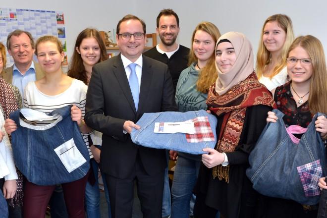 """Oberbürgermeister Thomas Kufen (Mitte) besucht das Juniorunternehmen """"BorBag"""" des Mädchengymnasium Essen-Borbeck und kauft einen Anteilsschein."""