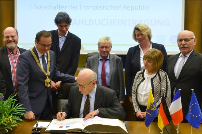 Im Beisein von Oberbürgermeister Thomas Kufen (mit Amtskette) und Vertreterinnen und Vertreter des Rates der Stadt Essen trägt sich der französische Botschafter S.E. Philippe Étienne ins Stahlbuch ein.