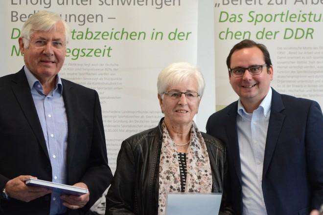 Oberbürgermeister Thomas Kufen (rechts) gratuliert Helmi Niehues zum Ablegen des 40. Sportabzeichens. Links im Bild Klaus Diekmann, Breitensportkoordinator im Essener Sportbund.