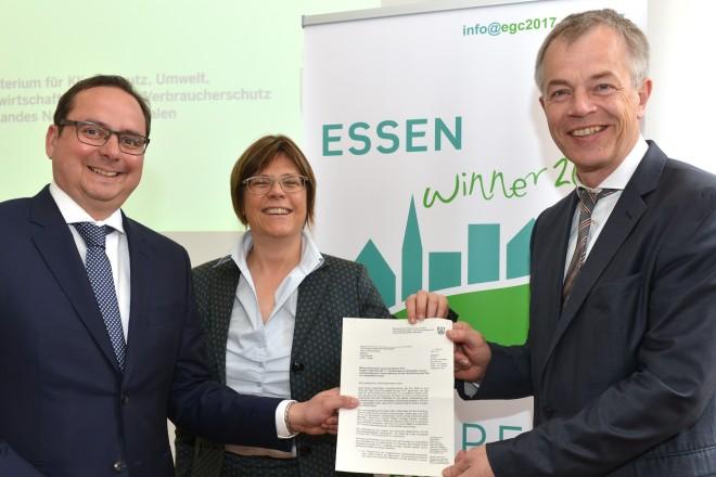 Oberbürgermeister Thomas Kufen (links) nimmt einen Scheck über 2,25 Millionen Euro für das Grüne Hauptstadt-Jahr 2017 von NRW-Umweltminister Johannes Remmel entgegen. In der Mitte Umweltdezernentin Simone Raskob.