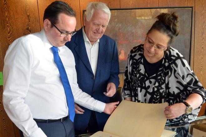 Oberbürgermeister Thomas Kufen (links) und Grafiker Helmuth Groth, der seit 40 Jahren die Seiten des Essener Stahlbuches gestaltet. Rechts im Bild Kerstin Uredat vom Amt für Ratsangelegenheiten und Repräsentation.