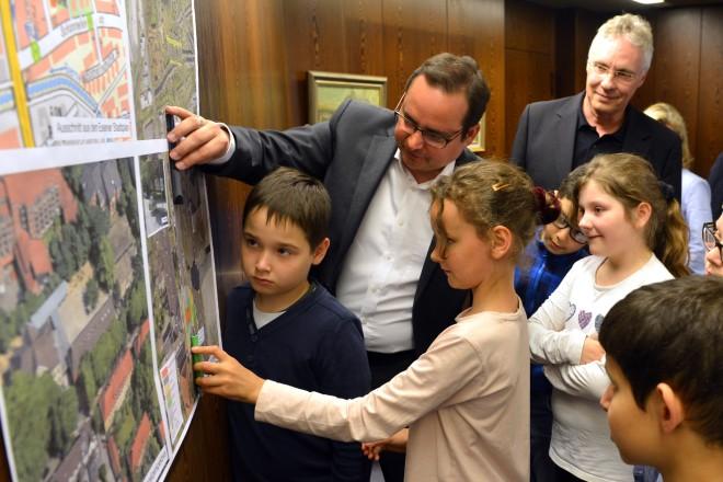 Oberbürgermeister Thomas Kufen (links) und der Leiter des Amtes für Straßen und Verkehr, Dieter Schmitz stellen den Schülerinnen und Schülern die geplante Verkehrsführung an der Bückmannshofschule vor.