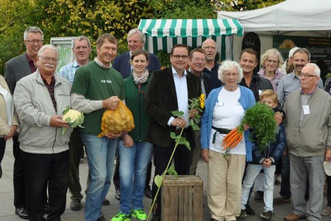 """Oberbürgermeister Thomas Kufen (Mitte mit Sonnenblume) besucht die Veranstaltung """"Essen erntet"""" im Grugapark."""