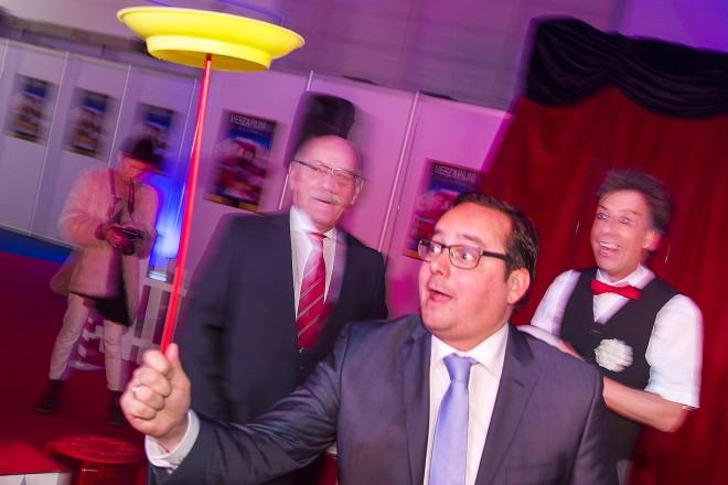 Impressionen vom Eröffnungsrundgang: Zirkus-Zauber und Jahrmarkt-Flair in Halle 4. Oberbürgermeister Thomas Kufen beweist seine Geschicklichkeit beim Tellerdrehen.