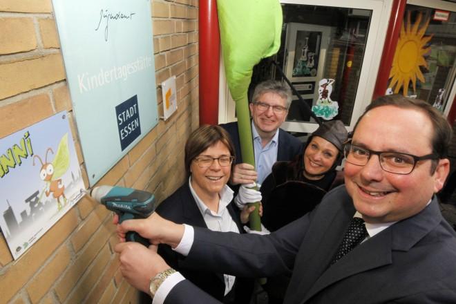 Foto: Oberbürgermeister Thomas Kufen bringt ein Schild an der Wand einer Kita an