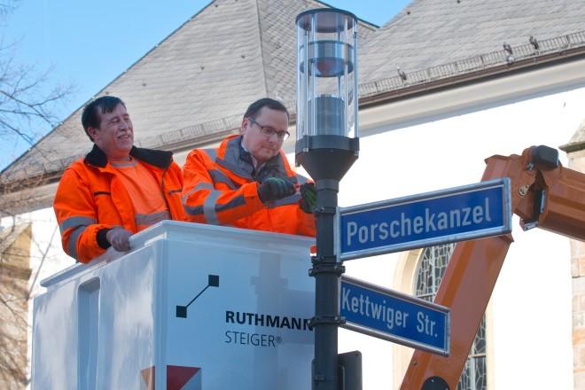 Oberbürgermeister Thomas Kufen tauscht an der Marktkirche eine der letzten verbliebenen alten Straßenlaternen durch ein modernes Energiespar-Leuchtmittel aus.