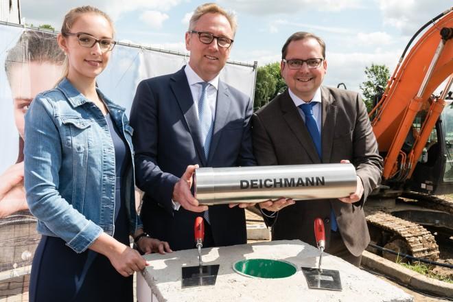 Firmenchef Heinrich Deichmann (Mitte) legte am 13. Juli 2017 gemeinsam mit Oberbürgermeister Thomas Kufen (rechts) sowie der Auszubildenden Ibanez Kozian (links) den Grundstein für das neue Bürogebäude in Essen.